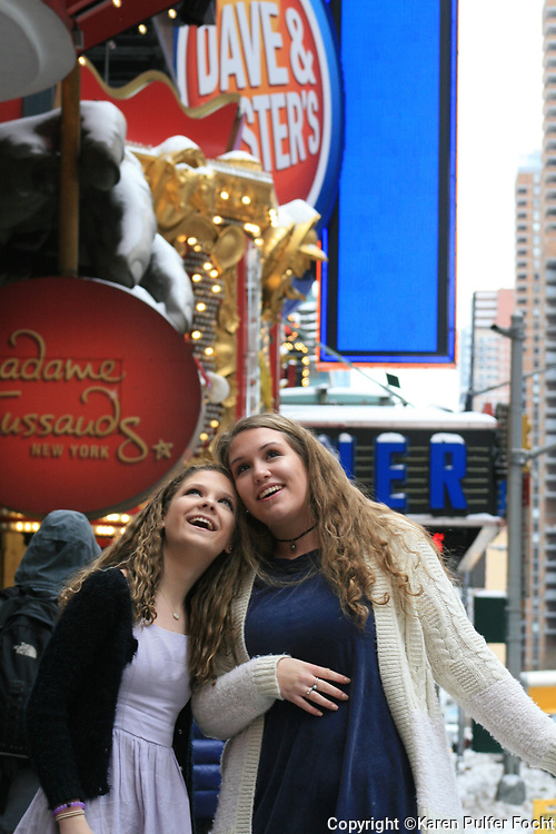 Two teenage girls enjoying a vacation in New York and seeing Time Square for the first time.