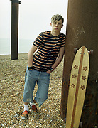 A young man standing on a beach with a surfboard.