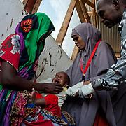 kenya, Dadaab, le 12-08-11 - centre de réception MSF du camp de Daghaley. Avec plus de 10000 nouveaux arrivants par semaine et plus de 400000 réfigiés, en majeure partie des somaliens ayant fuit la guerre et la famine qui sévissent dans leur pays, Dabaab est le plus grand camp de réfugiés au monde. À leur arrivée les enfants sont oscultés et enregistrés.