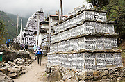 "In the Everest Area of Nepal: Mani stones are stone plates, rocks and/or pebbles inscribed, usually with mantra or ashtamangala, as a form of prayer in Tibetan Buddhism. Out of respect, people should walk to the left or clockwise around Mani Walls. Mani stones are placed in mounds or cairns along roadsides and rivers as an offering to spirits of place (or genius loci). The most common Tibetan prayer is ""Om Mani Padme Hum"", repeated to invoke compassion. Om Mani Padme Hum means ""Hail to the jewel in the lotus""."