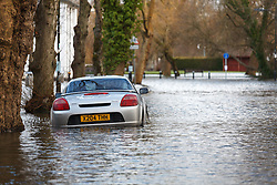 © Licensed to London News Pictures. 09/02/2014. Winchester, Hampshire, UK. A car engulfed by flood water on Park Avenue after water levels rose overnight in the historic city of Winchester in Hampshire. A flood warning has been issued by the Environment Agency for parts of the River Itchen. Photo credit : Rob Arnold/LNP