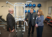 Hartman Middle School principal Geovanny Ponce, center, talks with Chief Middle Schools Officer Michael Cardona, left, and School Support Officer Deborah Crowe, right, in the new workout room during the dedication of the school's Health and Medical wing, April 3, 2014.
