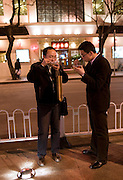 Men eat food from the Night Market, Wangfujing Street, Beijing, China