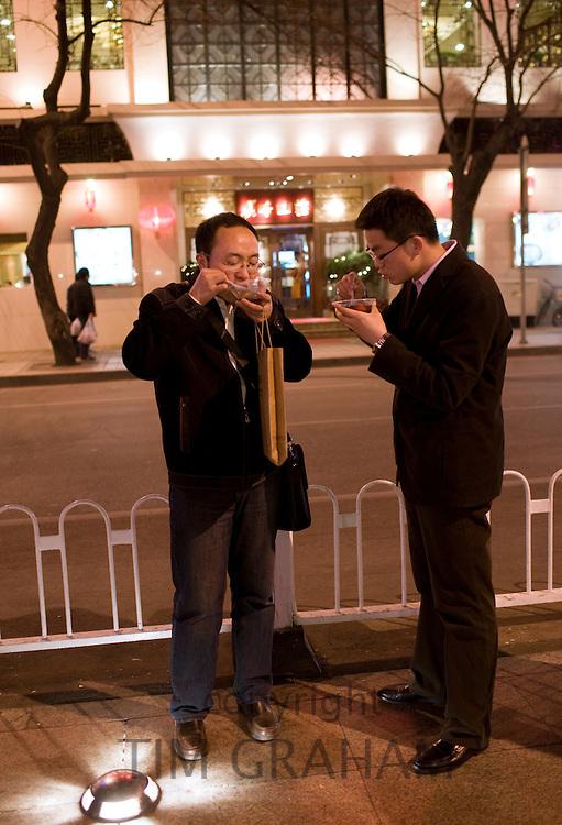 Men eat food from the Night Market, Wangfujing Street, Beijing, China
