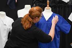 © Licensed to London News Pictures. 21/04/2020. Dukinfield, UK.   A woman puts the final touches as staff at Tibard begin working around the clock on an order of 5,000 units of nurses  uniforms (scrubs) for NHS workers per week in Dukinfield , owing to growing demand during the COVID-19 pandemic. The factory typically manufactures uniforms for the catering industry.  Photo credit: Ioannis Alexopoulos /LNP