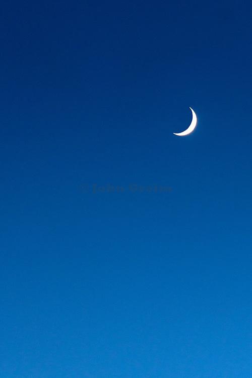 Crescent moon at dusk.