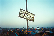 A sign 'Sacred Ground No Camping' at the Glastobury Festival, UK 1999