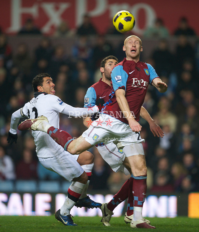 BIRMINGHAM, ENGLAND - Saturday, January 22, 2011: Aston Villa's James Collins clears the ball under pressure from Manchester City's Carlos Tevez during the Premiership match at Villa Park. (Photo by David Rawcliffe/Propaganda)