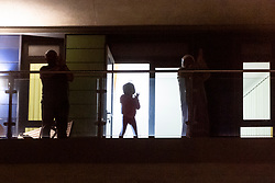 © Licensed to London News Pictures. 26/03/2020. London, UK. Home owners stand outside their balconies clapping and cheering in support of the National Health Service workers during the Coronavirus outbreak. Photo credit: Ray Tang/LNP