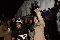 © Licensed to London News Pictures. 08/12/2014. London, UK. Helen Mirren switches on the Christmas tree lights. Dame Helen Mirren turns on the Christmas tree lights at Wapping Green in Tower Hamlets, East London tonight. This is the first time in many years that Wapping has had a Christmas tree and Dame Helen Mirren surprised residents by turning up at the community event and leading the countdown to switching the tree lights on. She then joined residents singing carols and drinking mulled wine, at the event which was arranged by the local councillor for Wapping and St Katharines, Julia Dockerill. Photo credit : Vickie Flores/LNP