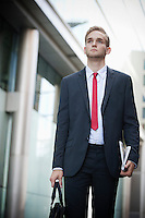 Young businessman in suit holding newspaper and bag