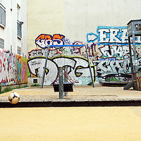Public playground in a backyard in Berlin. A young boy plays with a ball (not the boy in the picture) and just the flight of the ball is to see. In the background are bright walls of graffiti.
