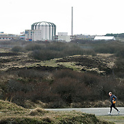 Nederland Petten 7 maart 2009 20090307 Foto: David Rozing ..Kerncentrale Petten, hardloper in duinlandschap.  Nuclear reactor for the production of medical isotopes to treat cancer. Nucleaire onderzoeksreactor, de snelle flux reactor In Petten wordt onder meer onderzoek gedaan naar manieren om de levensduur van radioactief afval te verkorten. Daarnaast worden er medische isotopen gemaakt, die gebruikt worden voor kankerbestrijding. Hoge Flux Reactor (HFR) op het terrein is onderzoeksreactor en levert ook radioactieve preparaten aan de medische sector t.b.v. diagnostiek en radiotherarpie (bestraling, radiofarmacie); voorheen Reactor Centrum Nederland (RCN) / Kerncentrale Petten..Foto: David Rozing/