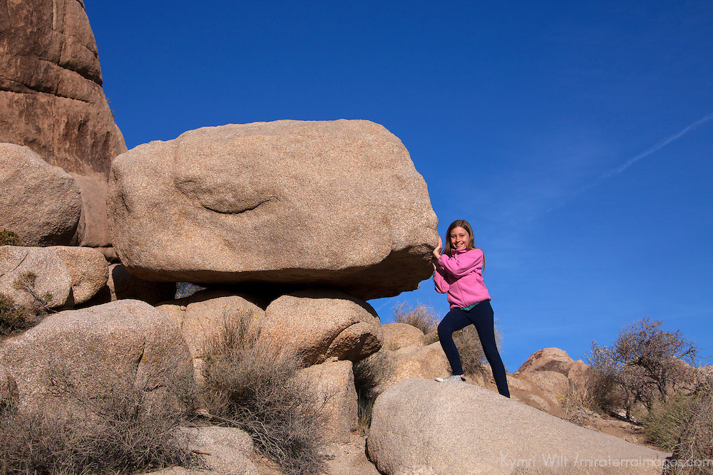 USA, California, Joshua Tree. Young girl and rock on Hidden Valley Trail in Joshua Tree National Park.