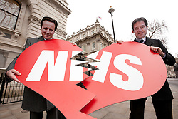 © Licensed to London News Pictures. 14/02/2012. LONDON, UK. Pulling apart a broken heart with NHS written across the front, two actors wearing masks depicting the British Prime Minister, David Cameron, and his deputy, Nick Clegg, stand next to the entrance to Downing Street on Valentines Day. The protest, organised by pubic sector union UNISON, was held to show the union's opposition to the government's proposed Health and Social Care bill that will see changes to the National Health Service. Photo credit: Matt Cetti-Roberts/LNP