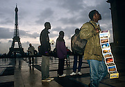 African street vendors wait for coach tourists to sell postcards near the Eiffel Tower, at the Trocadero, Paris.