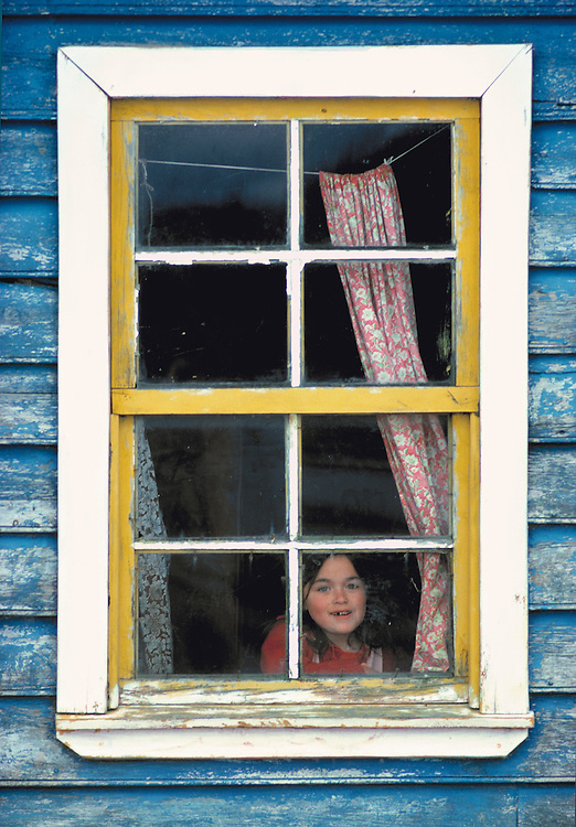 A girl smiles to friends through a paned window in Calbulco in central Chile.