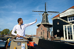 Captain/tour guide, Jeroen waves as he steers his open tour boat away from the dock on the Spaarne river near the Windmill the Adriaan.<br /> <br /> After living abroad for more than three years I visited my old home town. Wondering what has changed I packed both my curiosity and a camera. (Original posted as part of a photo essay 'Revisiting Familiar Grounds' here: http://www.basslabbers.com/WP/?p=1320)