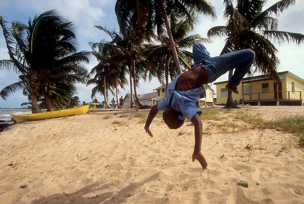 Belice.  Placencia..Un niño hace piruetas en la playa de Seine Bight..© JOAN COSTA