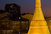 Golden glow of Shwe Phone Pwint Pagoda with old city in Eastern Bordertown, Yangon