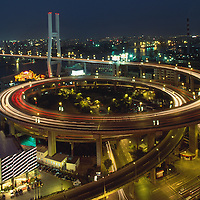 China, Shanghai, Nighttime traffic lights on stacked overpasses at entrance to Nanpu Bridge above Huangpu River