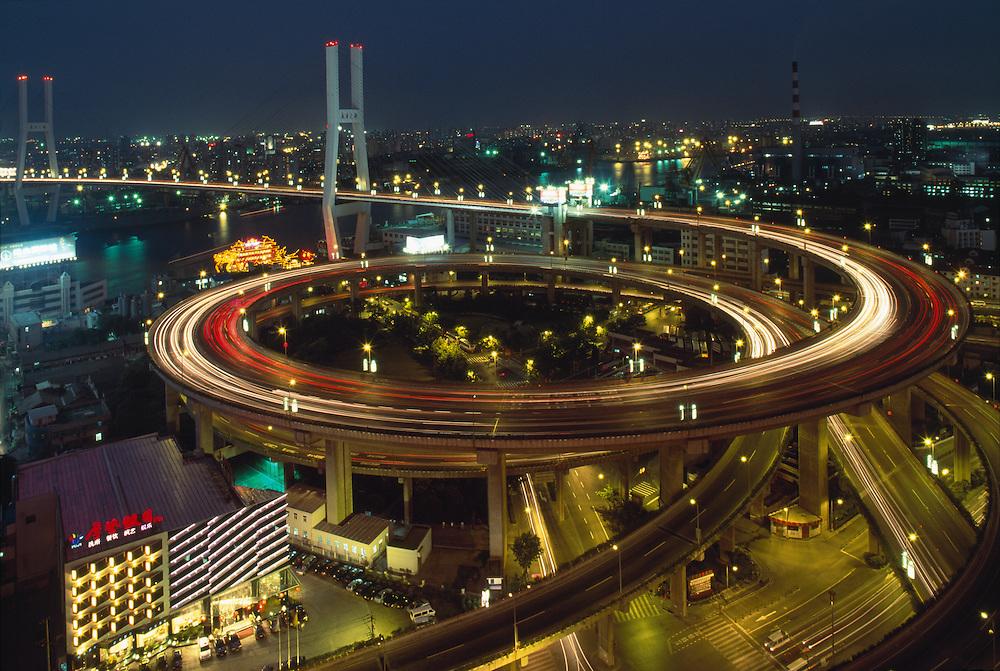 China, Shanghai, Nighttime traffic lights on stacked overpasses at entrance to Nanpu Bridge above Huangpu River