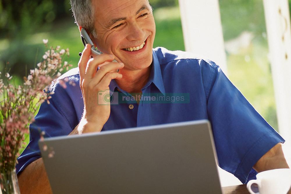 Dec. 14, 2012 - Man using laptop computer and cellphone (Credit Image: © Image Source/ZUMAPRESS.com)