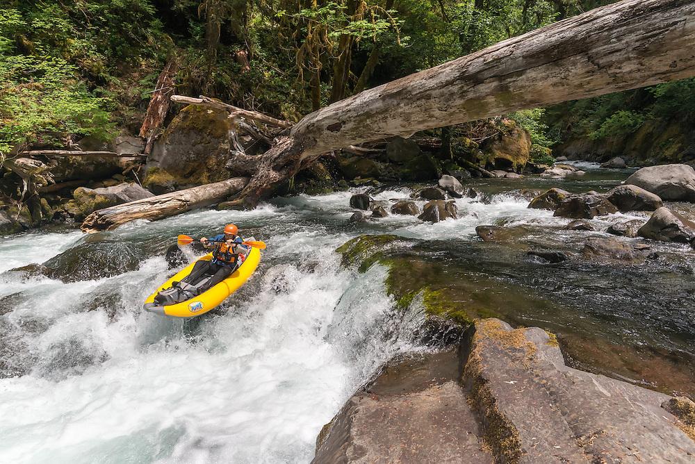 Paddling an inflatable kayak down a rapid on Salmon Creek, Oregon.