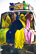 Women in colorful saris traveling in an overloaded three wheeled tuk tuk.<br /> (Photo by Matt Considine - Images of Asia Collection)