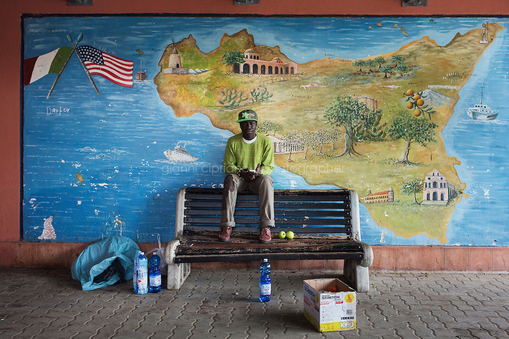 MINEO, ITALY - 26 NOVEMBER 2014: Modou Fall, a 20 years old asylum seeker from Gambia, sits on a bench by the cafeteria of the CARA (Accommodation Centre for Asylum Seekers) in Mineo where approximately 4,000 asylum seekers live, in Mineo, Italy, on November 26th 2014.<br /> <br /> By law, asylum-seekers can be held for 35 days in a CARA. In reality, the average stay is closer to a year.The Cara is located at the &quot;Residence degli Aranci&quot; (Residence of the Oranges), a small town built to accomodate the families of US soldiers operating at the Naval Air Station of Sigonella 40km away. Since 2011 the &quot;Residence degli Aranci&quot; hosts the Accommodation Center for Asylum Seekers, which has since then hosted more than 12,000 seekers of 47 nationalities and over 200 ethnic groups. The CARA of Mineo includes 404 houses. Each house hosts from 7 to 11 asylum seekers.