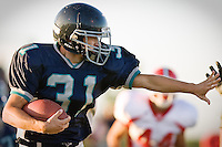 JEROME A. POLLOS/Press..Lake City's Tanner Schalk throws up a stiff-arm while making his way past the line of scrimmage in Friday's game against Sandpoint.