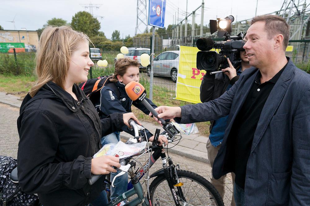 """Nederland, Den Bosch, 20110912.?Omroep Brabant TV maakt op namen bij overwegcontrole met BN-er Pauline Wingelaar van Gooische Meisjes in Den Bosch. Spoorwegovergang Orthen. Jongeren op weg naar school krijgen voorlichting van Prorail bij de overweg. De jongeren krijgen een zadeldekje en een lampje. .Dagelijks steken mensen die over als de bellen rinkelen, de lichten op rood staan en de bomen gesloten zijn. Dat kan levensgevaarlijke situaties opleveren..Nu de scholen weer zijn begonnen, gaat ProRail  en polite er vooral op letten dat brugklassers veilig de spoorwegovergangen oversteken. .Van Prorail gaan de BOA's, de buitengewoon opsporingsambtenaren, dit werk doen.? .Netherlands, Den Bosch, 20110912. ?Control with actrice Pauline Wingelaar known from the tv play """"Gooische Meisjes"""" in Den Bosch.at level crossing in Den Bosch. Youngsters on their way to school get information from Prorail at the level crossing..While the half-arm barriers are closing, many cyclists are on the crossing. A dangerous situation..Daily people cross while bells ring, red lights are flashing and the barriers are closed. This can be a llife threatening situation..Now the schools have started again, going ProRail and the police pay particular attention to the first graders safely cross railway crossings."""