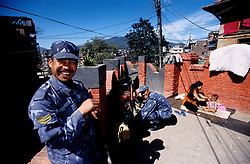 Kathmandu, 13 February 2005. Policemen on duty. A mother is dressing up her daughter.