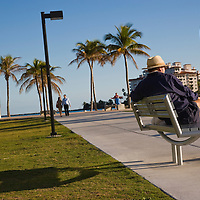 Man with hat sitting on a bench at South Point Park, South Beach, Florida, USA