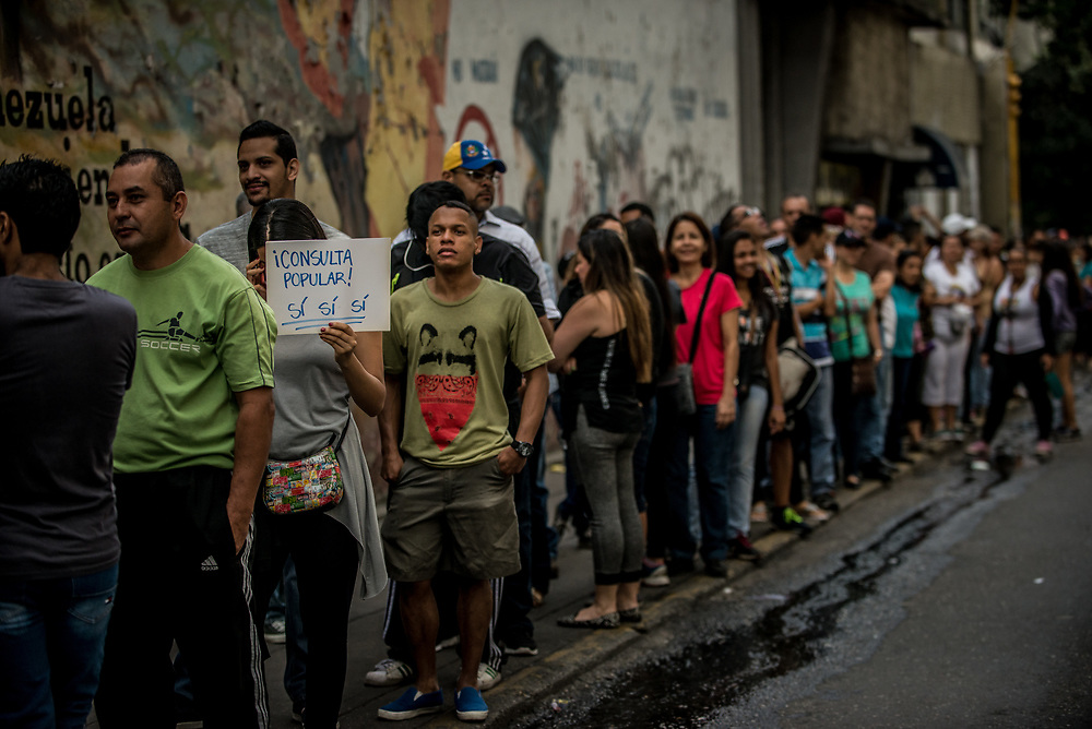 "CARACAS, VENEZUELA - JULY 16, 2017: A woman holds a sign that says, in Spanish: ""Popular Consultation: Yes, Yes, Yes"" - Meaning that she will vote ""Yes"" to each of the three questions on the ballot. Hundreds of people wait in line to vote in Caracas. Today, at over 2,000 polling locations, Venezuelans participated in a symbolic vote, called by the political opposition to the Socialist government. Ballots had three questions: ONE - Do you refuse the government's plans for a new constituent assembly, without prior approval from the people, TWO - Do you demand that government employees obey and defend the 1999 Constitution and respect the decisions of the National Assembly, and THREE - Do you approve that powers should be established by the Constitution, and that we should have free and transparent elections? The opposition held this vote, as a massive act of civil disobedience to show that the people disapprove of the government. For over 3 months, anti-government protests have raged across Venezuela.  PHOTO: Meridith Kohut"