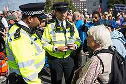 London, UK. 3 September, 2019. Police officers issue arrest warnings to Quakers blocking one of the two main access roads to ExCel London on the second day of week-long protests against DSEI, the world's largest arms fair. Protests were themed around faith and prayer and involved believers deriving from multiple faiths including the Quakers standing in solidarity against arms sales.