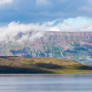 Clouds rolling across the sky create a pattern of shadows and sunlight on the spectacular glacially carved cliffs of Isafjardardjup. West Fjords, Iceland. July.