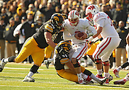November 02 2013: Wisconsin Badgers quarterback Joel Stave (2) is sacked by Iowa Hawkeyes defensive lineman Louis Trinca-Pasat (90) and Iowa Hawkeyes linebacker James Morris (44) during the first half of the NCAA football game between the Wisconsin Badgers and the Iowa Hawkeyes at Kinnick Stadium in Iowa City, Iowa on November 2, 2013. Wisconsin defeated Iowa 28-9.