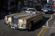A 1960 Bentley S2 Continental drives down the Kings Road, Chelsea. A couple pass along the street in west London with the roof down, the sun glinting off their bumper (fender) and onto them on a perfect late-summer afternoon. The scene echoes a bygone era when drivers and passengers would parade down here to show off their motors - this still happens today. The Bentley S2 (and the high-performance Bentley Continental S2 derived from it) was a luxury car produced by Bentley from 1959 until 1962. 1,920 standard and long-wheelbase car chassis were built between 1959 and 1962. Almost all were fitted with standard factory bodywork. A number had coachbuilt bodies by Park Ward, Hooper, H. J. Mulliner & Co., and James Young.