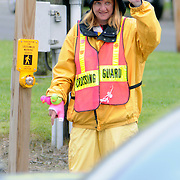 "5/18/11 -- BRUNSWICK, Maine.  Lisa Green, crossing guard at the corner of Longfellow and Maine streets in Brunswick, has a wave or a smile for nearly every passerby. Her habit of wearing funny hats began last year when serving near Jordan Acres School.   ""I was clipped,"" she said, ""and it hurt!""  The guy {who hit me} kept saying that he didn't see me -- so I decided to start making it impossible to not see me."" She added, "" My best hats come out at Halloween!""  Photo by Roger S. Duncan."