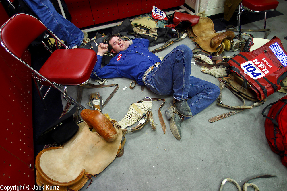 "08 DECEMBER 2002 - LAS VEGAS, NEVADA, USA: Mike Outhier, a saddle bronc rider from Utopia, TX, relaxes in the saddle bronc locker room at the Thomas and Mack Center before the third round of the National Finals Rodeo in Las Vegas, NV, Dec. 8. 2002. The NFR is the ""Super Bowl"" of rodeo, only the top 15 cowboy from each of the Professional Rodeo Cowboy's Association are invited to participate, which runs for 10 days in Las Vegas, NV.  PHOTO BY JACK KURTZ"