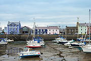Pleasure boats in harbour at low tide and bright painted harbourside housing and The Harbourmaster Hotel in Aberaeron, Pembrokeshire, Wales, UK
