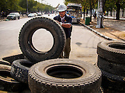 """30 DECEMBER 2013 - BANGKOK, THAILAND:  An anti-government protestor rolls a tire to a barricade he was reinforcing at a checkpoint. Violence around the anti-government protest sites has escalated in recent days and several protestors have been hurt by small explosive devices thrown at their guard posts. As a result, protestors are fortifying their positions with sandbags and bunkers. Suthep Thaugsuban, the leader of the anti-government protests in Bangkok, has called for a new series of massive protests after the 1st of the year and said it the shutdown, or what he described was the seizure of the capital, would be the day when """"People's Revolution"""" would """"begin to end and uproot the Thaksin regime.""""         PHOTO BY JACK KURTZ"""