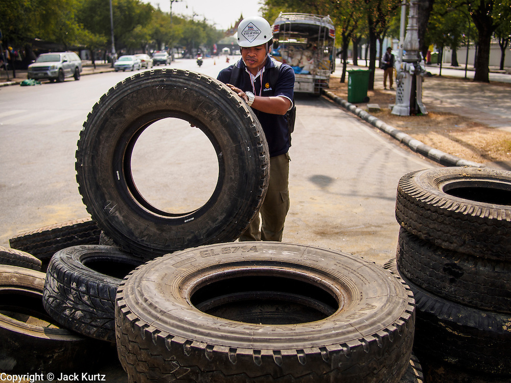 "30 DECEMBER 2013 - BANGKOK, THAILAND:  An anti-government protestor rolls a tire to a barricade he was reinforcing at a checkpoint. Violence around the anti-government protest sites has escalated in recent days and several protestors have been hurt by small explosive devices thrown at their guard posts. As a result, protestors are fortifying their positions with sandbags and bunkers. Suthep Thaugsuban, the leader of the anti-government protests in Bangkok, has called for a new series of massive protests after the 1st of the year and said it the shutdown, or what he described was the seizure of the capital, would be the day when ""People's Revolution"" would ""begin to end and uproot the Thaksin regime.""         PHOTO BY JACK KURTZ"