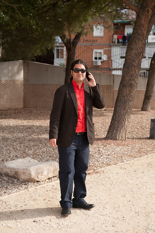 Standing portrait of a Spanish tour leader on his cell phone organizing the next step of the day's scheduled tour.