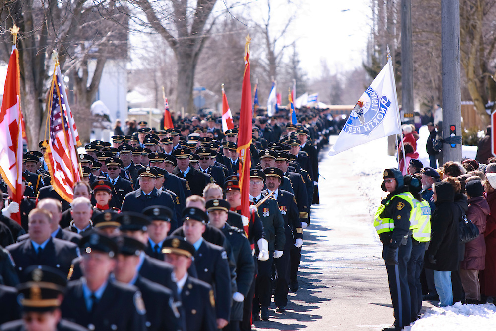Thousands of fire fighters from across Canada march through the streets of Listowel Ontario, Thursday, March 24, 2011 to honour fallen fire fighters Kenneth Rae and Raymond Walter who were killed fighting a blaze in a dollar store last Thursday when the roof collapsed.<br /> THE CANADIAN PRESS/ Geoff Robins