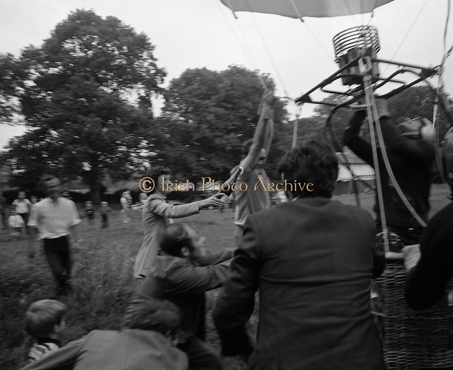 Dew Mighty Minerals Hot Air Balloon.   (H15)..1974..07.08.1974..08.07.1974..7th August 1974..The launching of the Dew Mighty Minerals hot air balloon,took place in Tullamore,Co Offaly last night,as part of the Tullamore Festival Week. The balloon was piloted by Mr Wilf Woollett,a veterinary surgeon from Loughrea,Co Galway and his co-pilot was Kevin Haugh. Miss Rosemary Mannion,the Offaly Rose of Tralee contestant sent the balloon on its way by popping a bottle of Champagne over it.  The balloon itself has a capacity of 56,000 cubic feet,is 60ft high and 50ft wide. It is made from nylon/polyproplene. The basket is 2ft square by 3ft high and carries two people,it is attached to the balloon by steel cables..Wilf Woollett has piloted the balloon in the U.S. and Britain and is a member of the Dublin Balloon Club...With the balloon inflated,Offaly Rose, Rosemary Mannion is pictured as she rushes in with a bottle of Champagne to send it on its way.