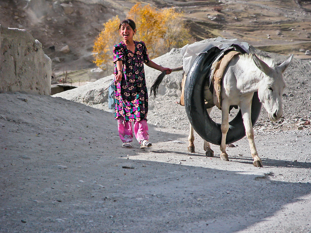 Portrait of a young girl who has just come up from the river to collect water for her family. The donkey is carrying the water inside the rubber inner tube!