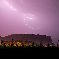 © Licensed to London News Pictures . 03/08/2014 . Cassis , France . Intense electrical storms sweep the South of France this morning ( Sunday 3rd August 2014 ) . Viewed from the town of Cassis , near to Marseille in the South of France , lightning strikes over the 1293 foot high Cap Canaille cliff - the highest sea cliff in Europe , overlooking the Mediterranean Sea and dwarfing the historic town's Medieval Castle , below . Photo credit : Joel Goodman/LNP