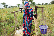 A girl carries two buckets of water she just filled from a UNICEF-sponsored pump in the village of Game, Guera province, Chad on Tuesday October 16, 2012.